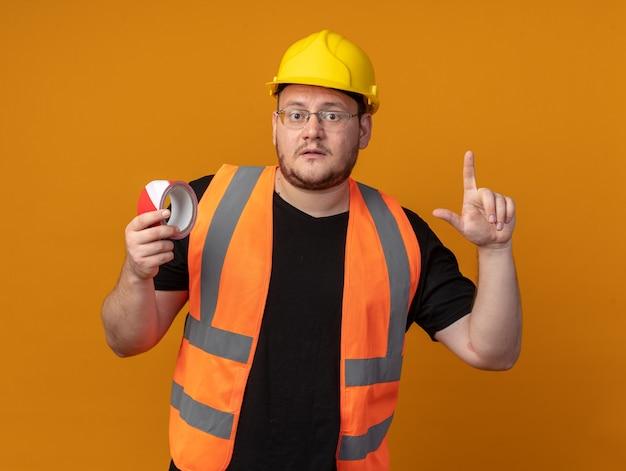 Hombre constructor en chaleco de construcción y casco de seguridad sosteniendo cinta adhesiva apuntando con el dedo índice hacia arriba mirando preocupado de pie sobre fondo naranja