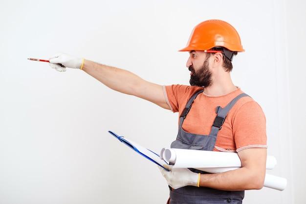Hombre constructor escribiendo en pedidos de clientes portapapeles. arquitecto contratista. concepto de renovación del hogar.