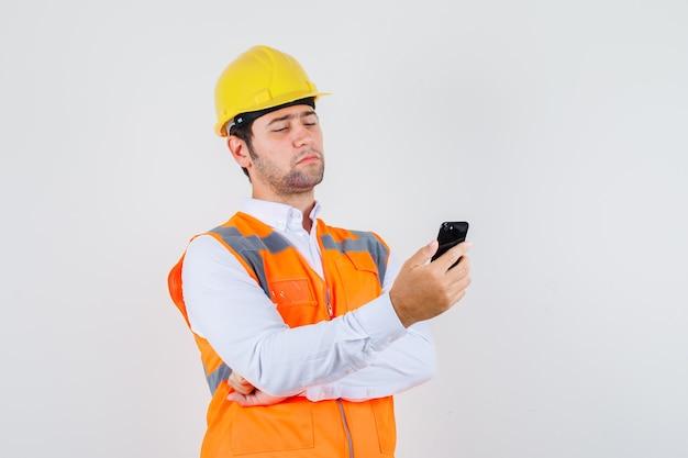 Hombre constructor mirando smartphone en camisa, uniforme y mirando pensativo, vista frontal.