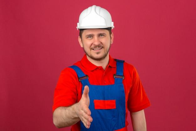Hombre constructor con uniforme de construcción y casco de seguridad sonriendo amigable haciendo gesto de saludo ofreciendo mano de pie sobre pared rosa aislado
