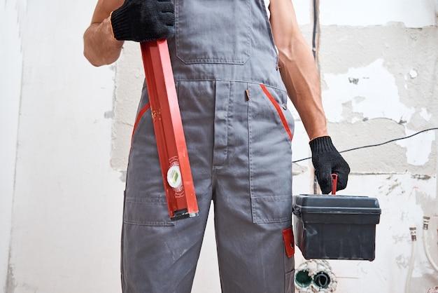 Hombre constructor en uniforme con herramientas de construcción