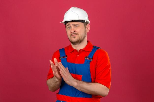 Hombre constructor vistiendo uniforme de construcción y casco de seguridad aplaudiendo con mirada segura de pie sobre pared rosa aislado