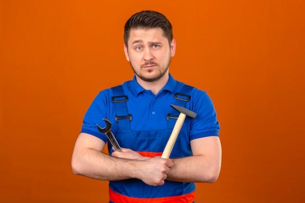 Hombre constructor vistiendo uniforme de construcción y casco de seguridad de pie con los brazos cruzados con un martillo y una llave en las manos con cara seria sobre pared naranja aislada