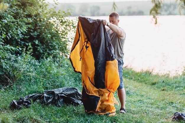 Hombre construir tienda en la naturaleza al atardecer cerca del lago durante la pesca