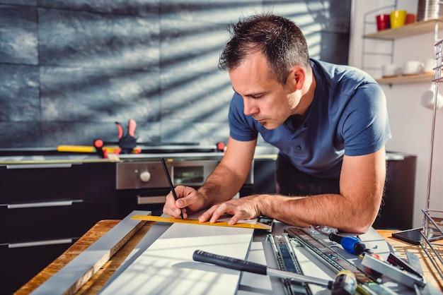 Hombre construyendo armarios de cocina