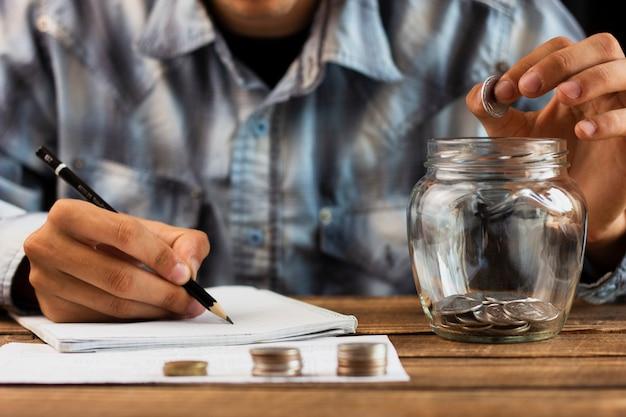 Hombre contando monedas de ahorro de jarra