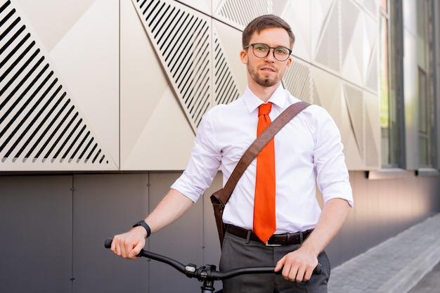 Hombre contemporáneo en anteojos y ropa formal mirándote mientras avanza a lo largo de la pared del edificio contemporáneo
