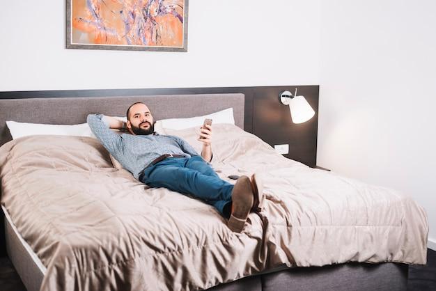 Hombre contento con teléfono posando en la cama
