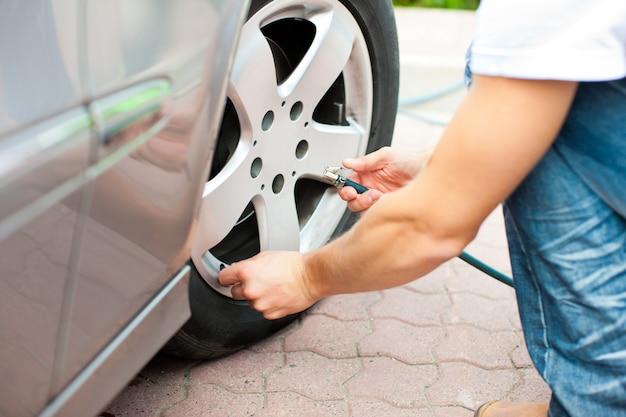 El hombre está controlando la presión de los neumáticos de su coche.