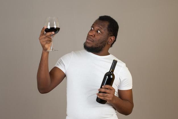 Hombre con copa de vino tinto en una mano y botella de vino en la otra, de pie frente a la pared gris