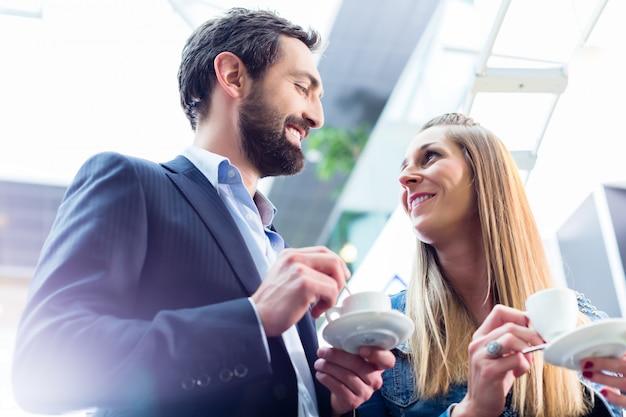 Hombre coqueteando con mujer mientras bebe café