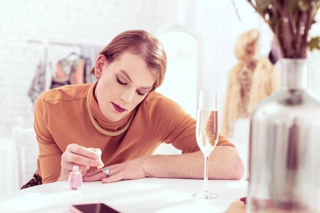Hombre coqueto de género-queer. hermoso hombre transgénero de pelo corto pintando su uña corta con esmalte de uñas rosa claro