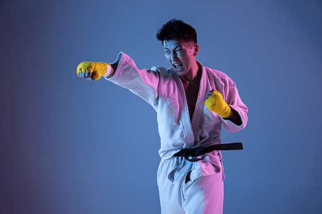 Hombre coreano confiado en kimono practicando combate cuerpo a cuerpo, artes marciales. joven luchador con cinturón negro entrenando en pared degradada con luz de neón. concepto de estilo de vida saludable, deporte.