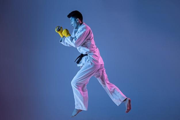 Hombre coreano confiado en kimono practicando combate cuerpo a cuerpo, artes marciales. joven luchador con cinturón negro entrenando sobre fondo degradado en luz de neón. concepto de estilo de vida saludable, deporte.