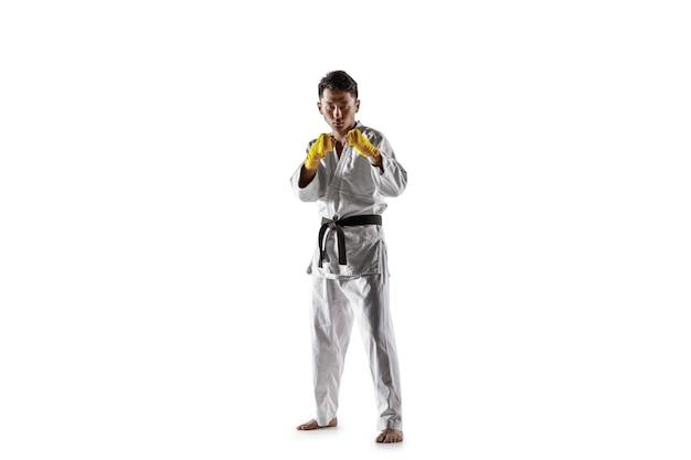 Hombre coreano confiado en kimono practicando combate cuerpo a cuerpo, artes marciales. luchador masculino joven con entrenamiento de cinturón negro aislado en la pared blanca. concepto de estilo de vida saludable, deporte.