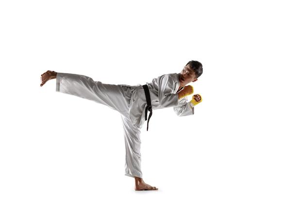 Hombre coreano confiado en kimono practicando combate cuerpo a cuerpo, artes marciales. luchador masculino joven con entrenamiento de cinturón negro aislado sobre fondo blanco de estudio. concepto de estilo de vida saludable, deporte.