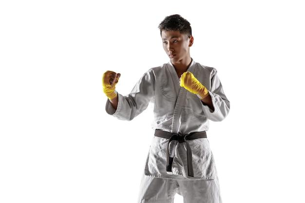Hombre coreano confiado en kimono practicando combate cuerpo a cuerpo, artes marciales.