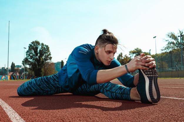 Hombre corredor estirando las piernas preparándose para correr entrenamiento en pistas del estadio haciendo calentamiento