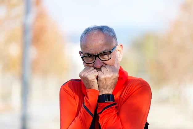 Hombre corredor senior con gafas de sol cubriendo la boca con las manos al aire libre