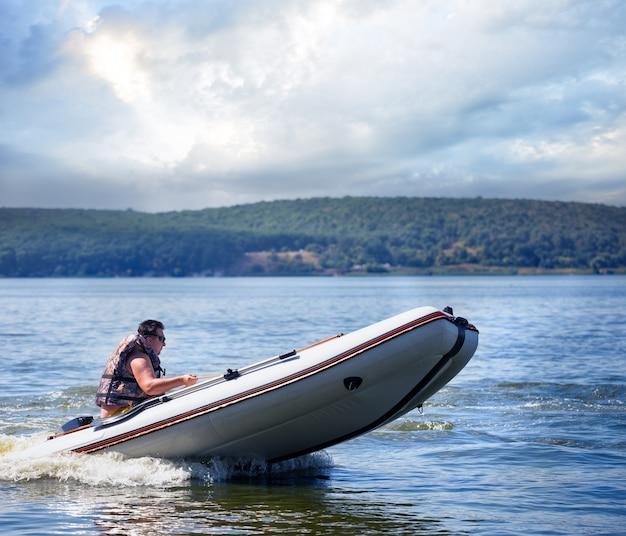 Hombre corriendo bote a motor blanco con rayas naranjas en los lados