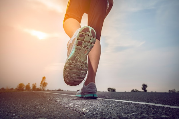 Hombre corriendo en una carretera con el sol.