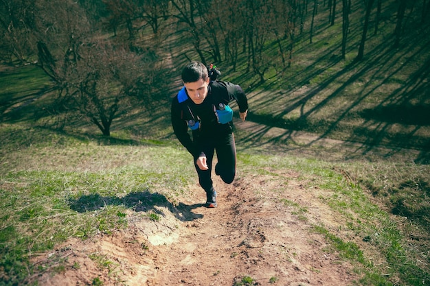 Hombre corriendo en un parque o bosque contra árboles