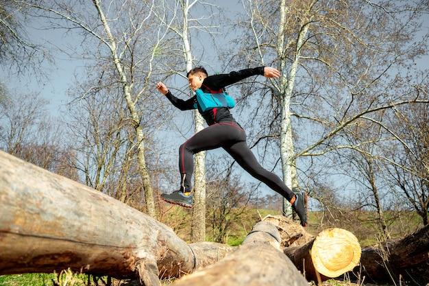 Hombre corriendo en un parque o bosque contra el espacio de árboles