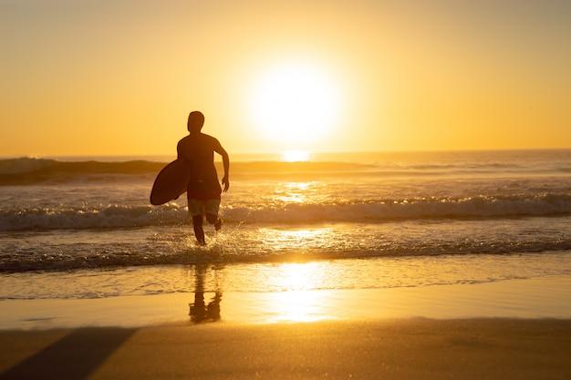 Hombre corriendo con tabla de surf en la playa