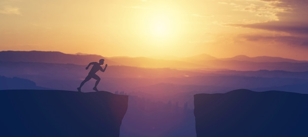 Hombre corriendo towars acantilado en las montañas.