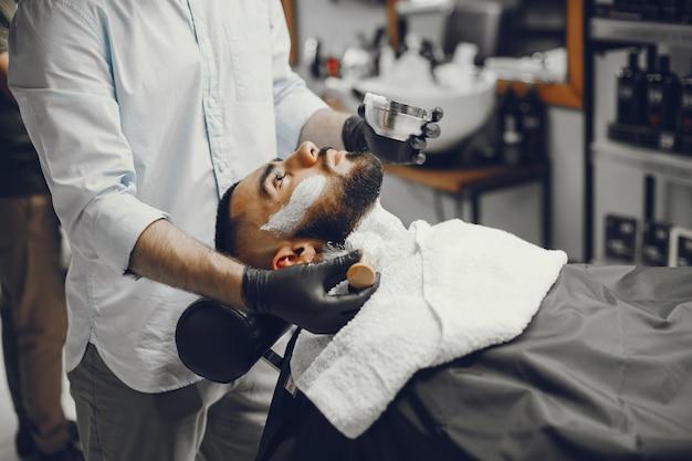 El hombre se corta la barba en la barbería.