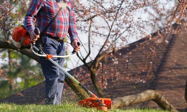 El hombre corta el césped con una cortadora de césped.