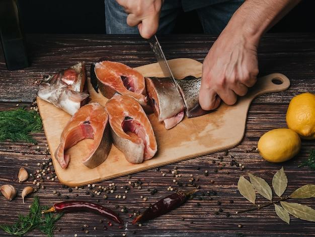 El hombre corta un cuchillo de trucha fresca cruda en trozos para cocinar