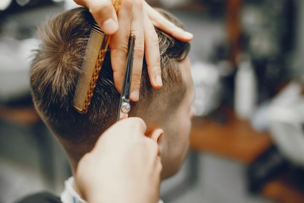 Un hombre corta el pelo en una barbería.