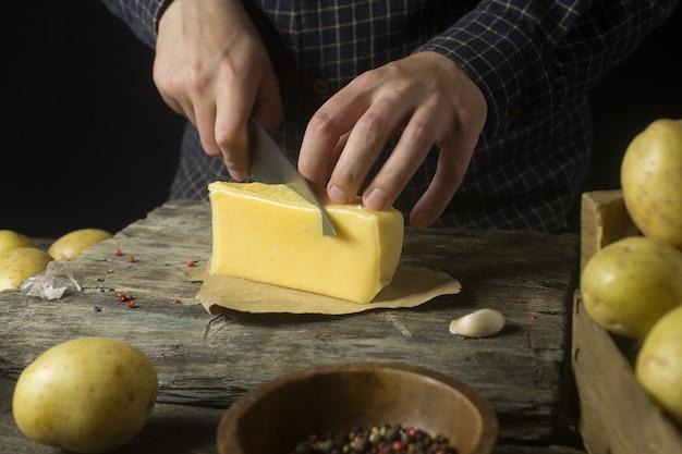 Hombre corta queso en la cocina sobre una mesa de madera rústica