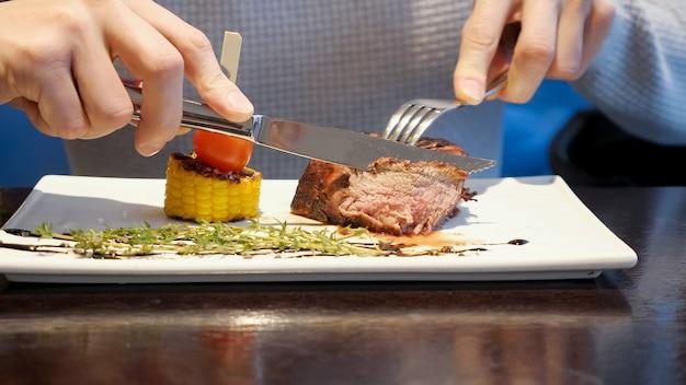 El hombre corta un trozo de bistec y come en el café, cerrar
