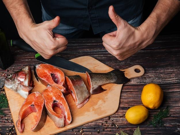 Hombre corta trucha cruda fresca en trozos para cocinar