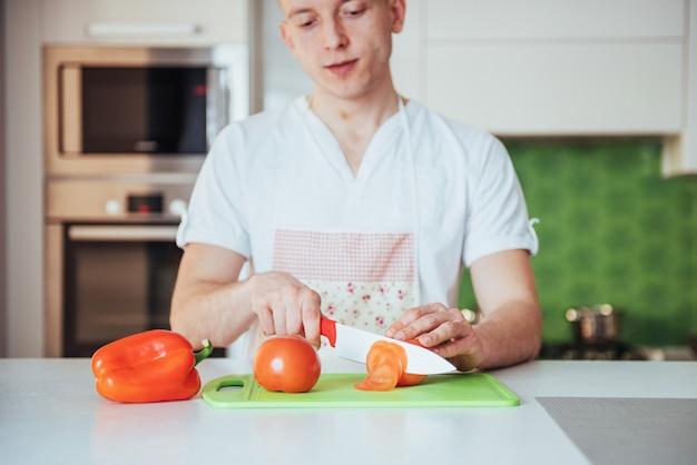 El hombre corta las verduras juntas en la cocina