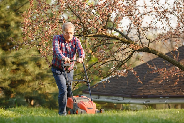 Hombre con cortadora de césped eléctrica, cortar el césped. jardinero podando un jardín. día soleado, suburbio, pueblo. hombre adulto poda y paisajismo jardín, podar césped, césped, caminos. trabajo duro en la naturaleza.