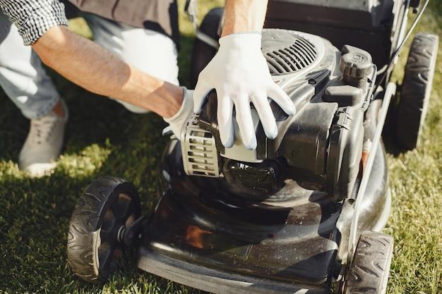 Hombre cortando césped con cortadora de césped en el patio trasero. hombre con delantal negro. reparaciones de chico.