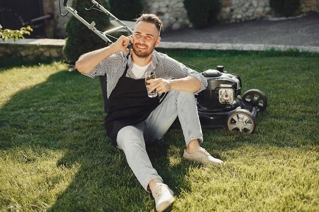 Hombre cortando césped con cortadora de césped en el patio trasero. hombre con delantal negro.