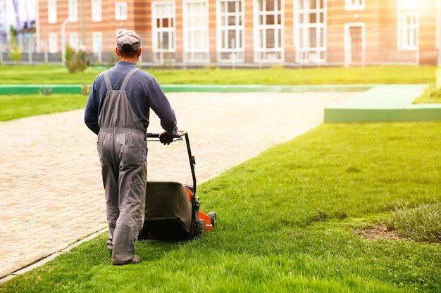 Hombre cortando césped verde con cortadora de césped en el patio trasero. fondo de estilo de vida del país de jardinería.