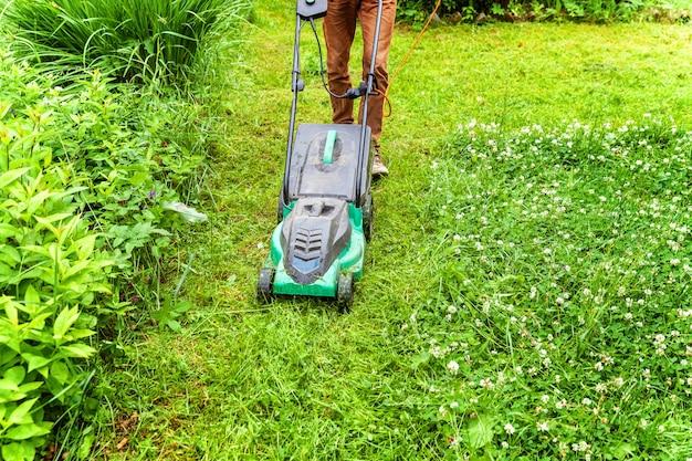 Hombre cortando césped verde con cortadora de césped en el patio trasero. fondo de estilo de vida del país de jardinería