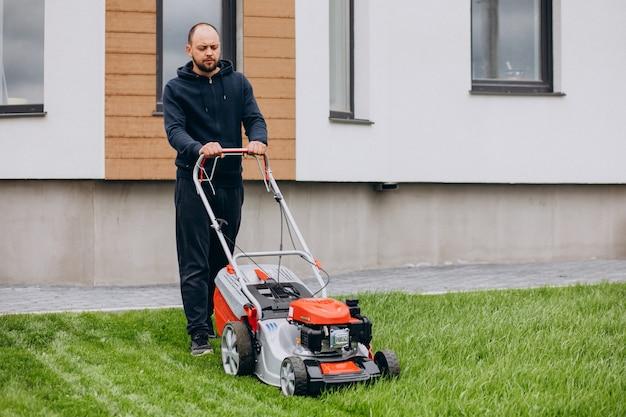 Hombre cortando hierba con césped en el patio trasero