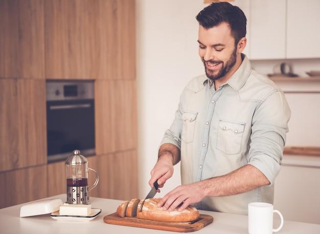 El hombre está cortando pan y sonriendo mientras hace sándwiches