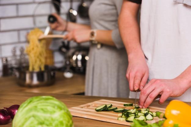Hombre cortando pepinos y mujer cocinando pasta