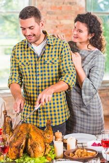 Hombre cortando pollo al horno en mesa cerca de mujer