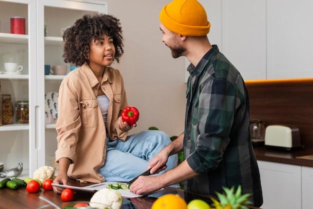 Hombre cortando verduras y mirando a su novia