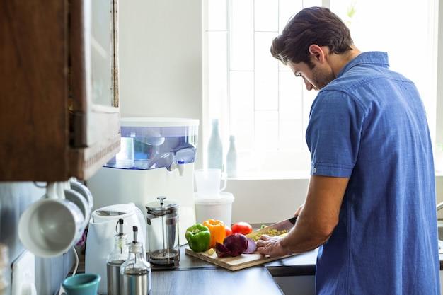 Hombre cortando verduras en el mostrador de la cocina