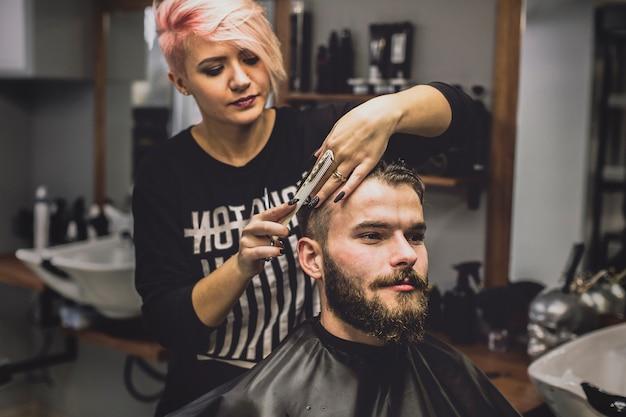 Hombre de corte de pelo de mujer en el salón