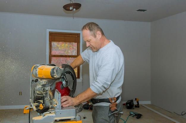 El hombre cortó la moldura de madera con sierra circular